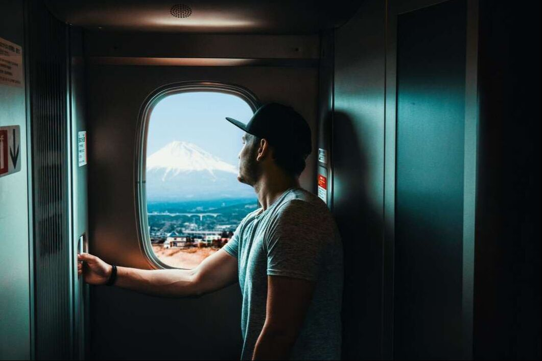 A man on a train taking in the views over the Fuji mountain